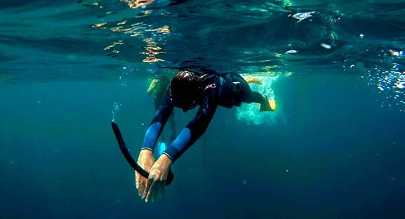 A female freediver at the surface of the sea holding a snorkel in her hands ready to do a duck dive in the blue water
