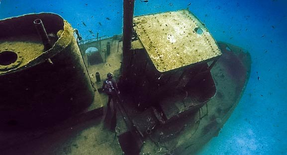 Freediver exploring the front of a shipwreck that lies upright on a sand bottom