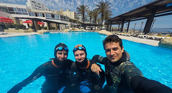 Three freedivers in an outdoor pool facing the camera with palm trees in the background