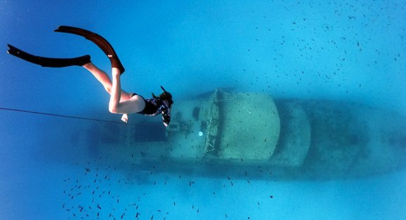 Freediver in a red wetsuit looking at a shipwreck while holding the freediving line